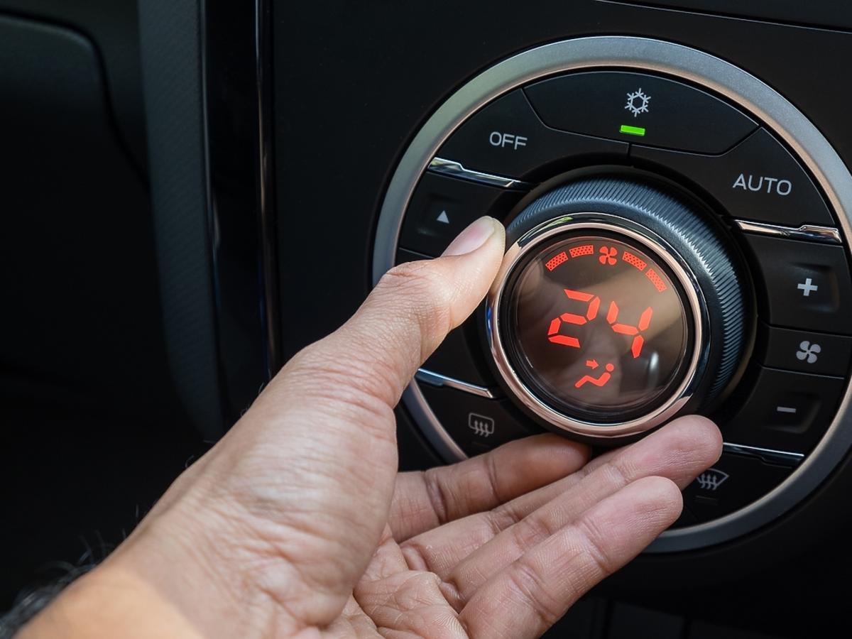 Mężczyzna ustawia temperaturę klimatyzacji w samochodzie.