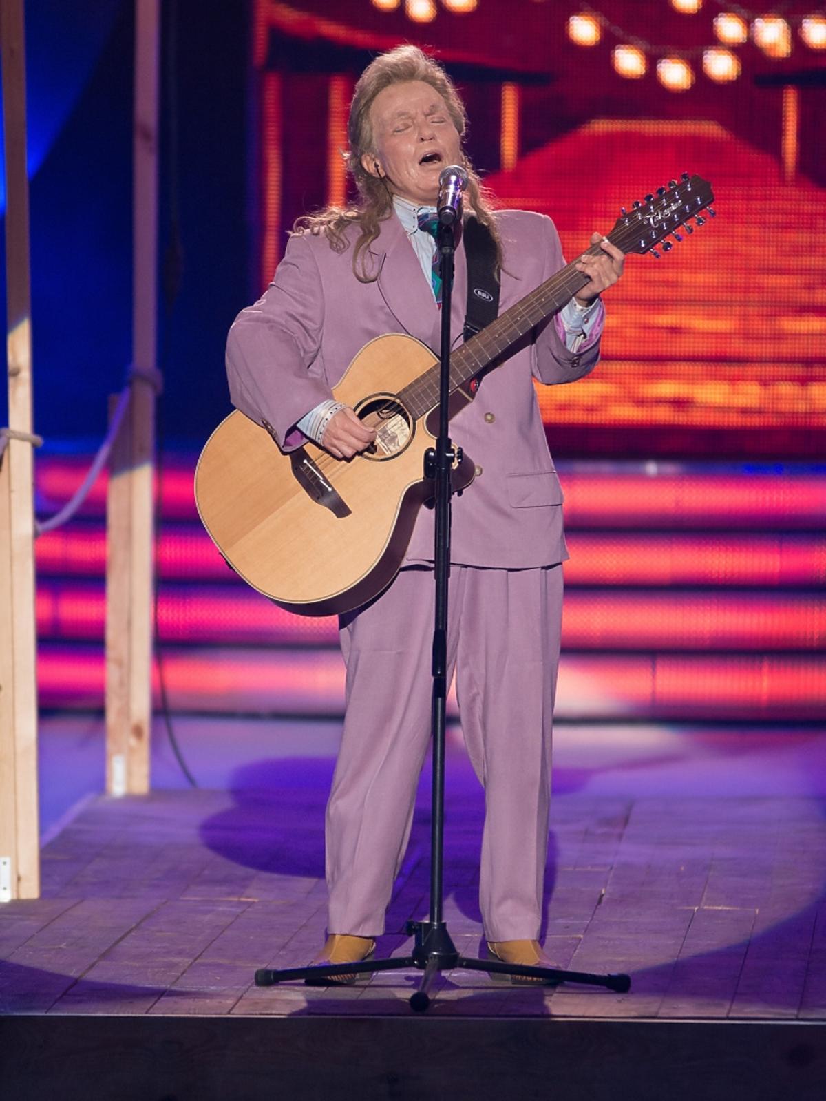 Mężczyzna w fioletowym garniturze z gitarą