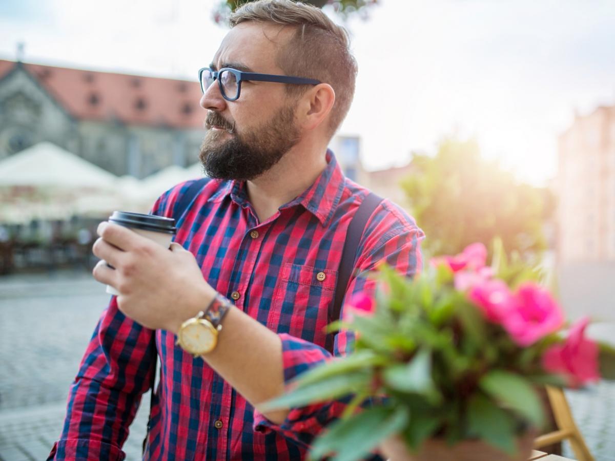 Mężczyzna w koszuli w kratę z kawą