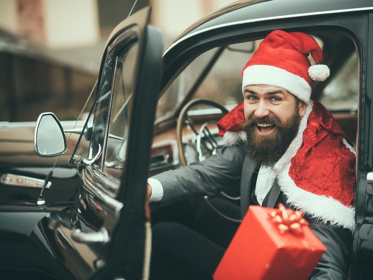 Mężczyzna w stroju mikołaja wychodzi z samochodu z prezentem.