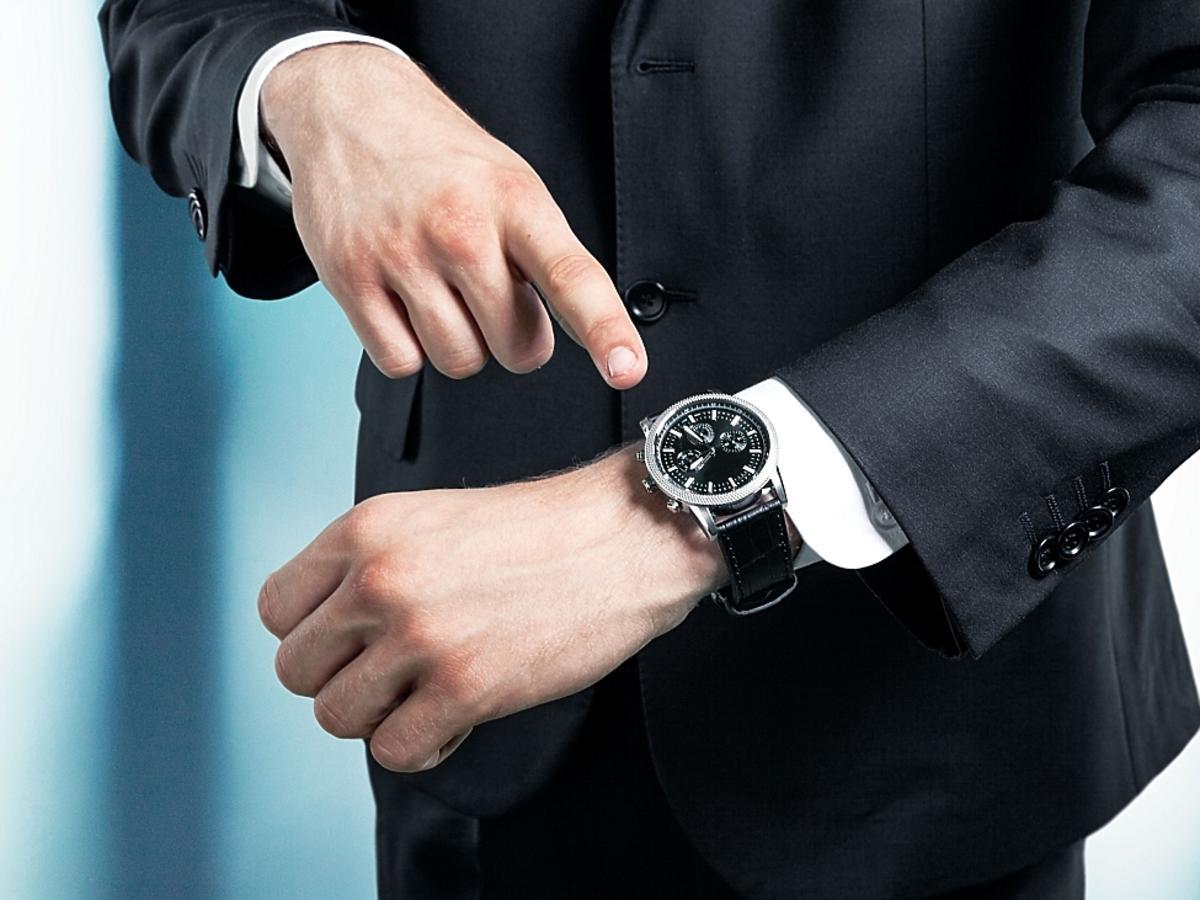 mężczyzna wskazujący na zegarek
