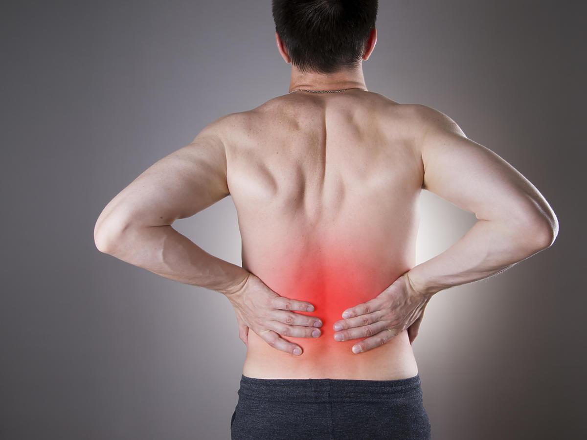 Mężczyzna z bólem nerek trzyma się za plecy