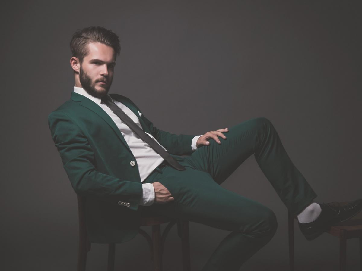 Mężczyzna z brodą w zielonym garniturze