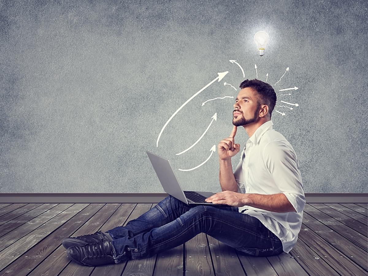 mężczyzna z laptopem na podłodze