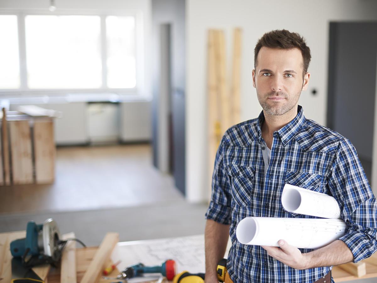 mężczyzna z projektami pod ręką