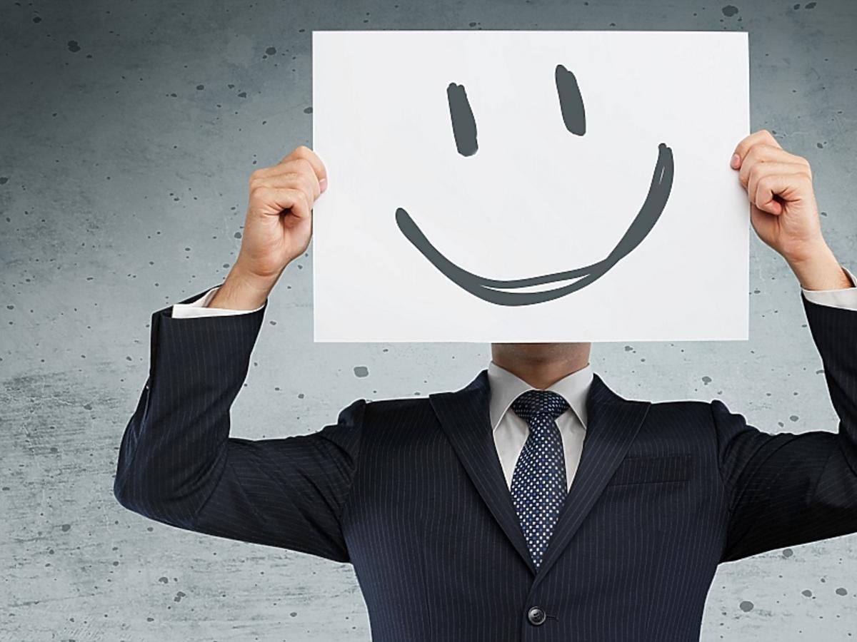 mężczyzna z uśmiechem narysowanym na kartce