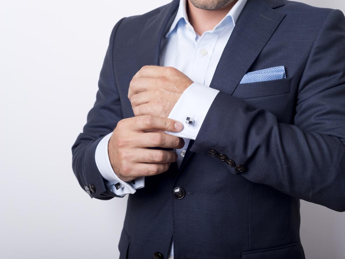 Mężczyzna zapinający spinki do mankietów