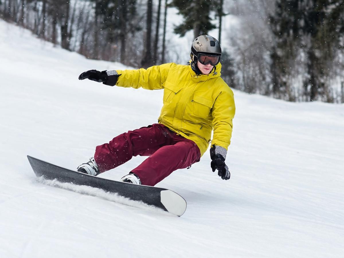 mężczyzna zjeżdża na desce snowboardowej