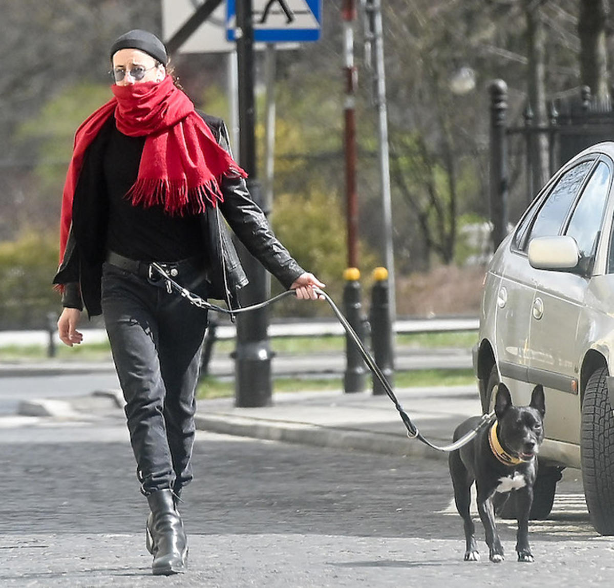 Michał Szpak na spacerze z psem owinięty czerwonym szalikiem