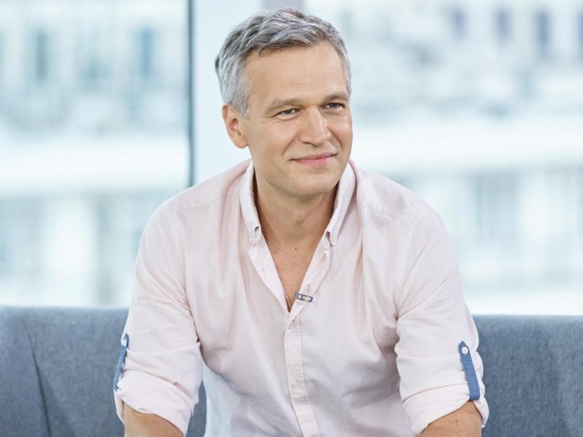 Michał Żebrowski siedzi na szarej kanapie