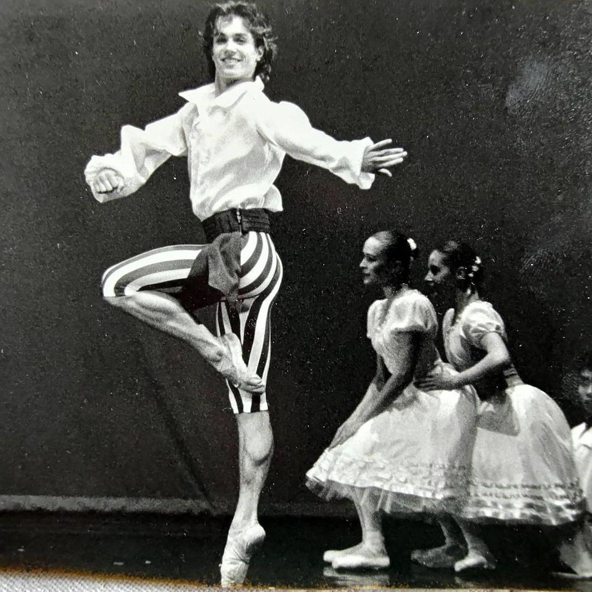 Misha Kostrzewski w białej koszuli i spadniach w paski tańczy balet