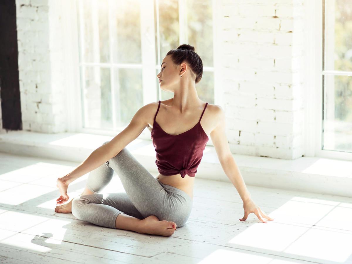 Młoda dziewczyna gimnastykuje się na sali gimnastycznej