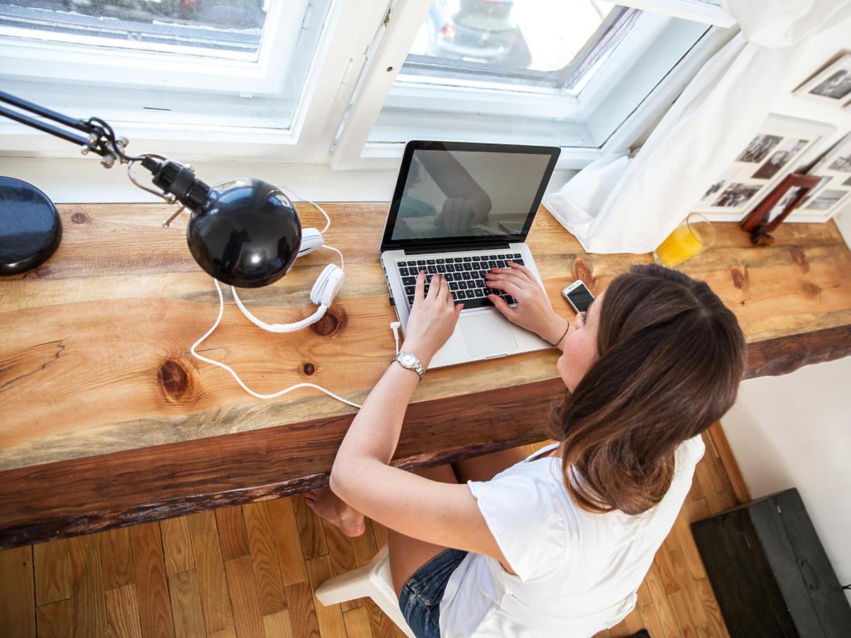 Młoda dziewczyna siedzi przy biurku i pracuje na komputerze