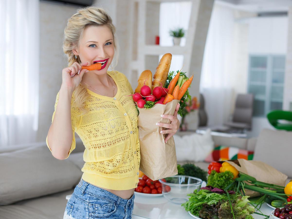 Młoda kobieta je warzywa.