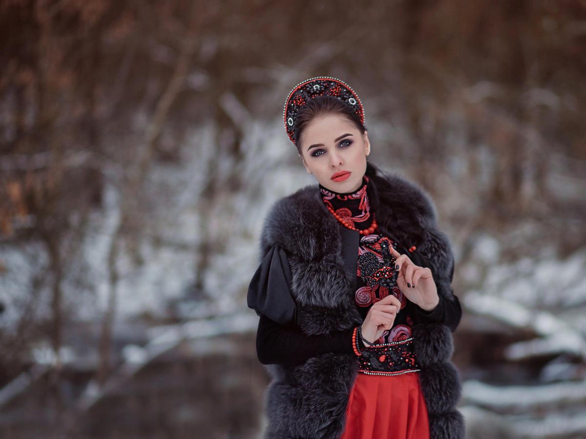 Młoda kobieta jest ubrana w ludowy strój i biżuterię w stylu folk.