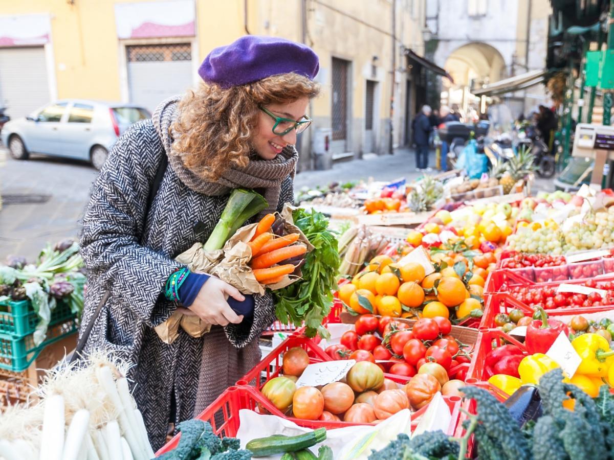 młoda kobieta kupuje warzywa na straganie ulicznym