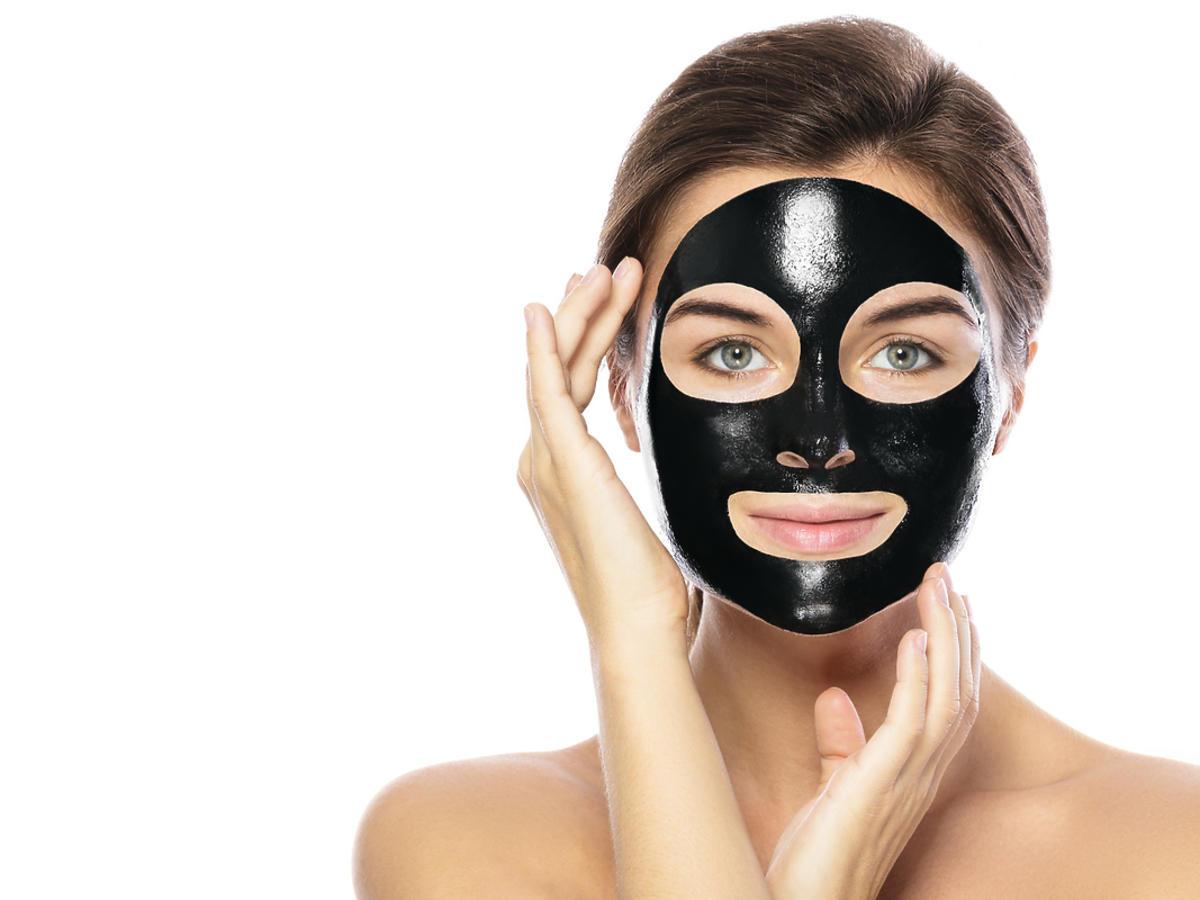 Młoda kobieta ma na twarzy czarną maskę.