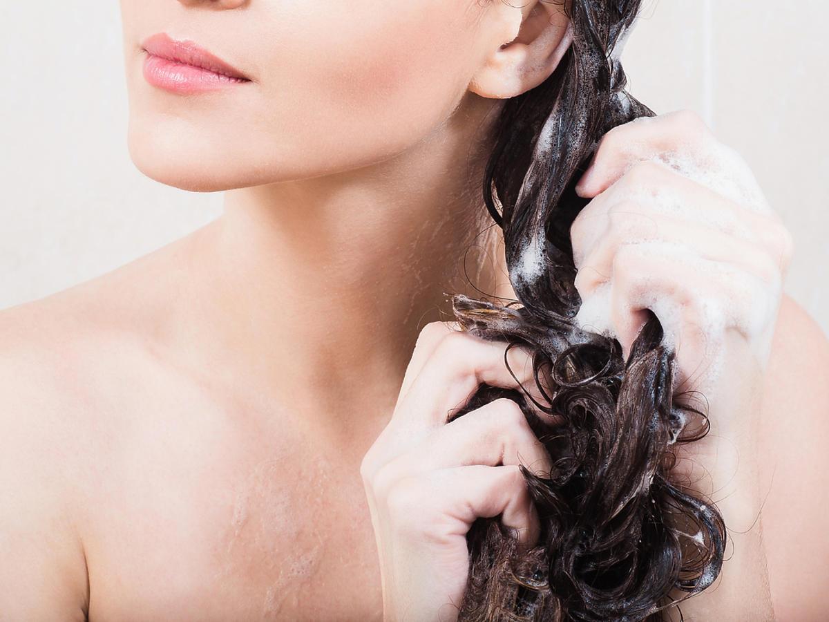 Młoda kobieta myje włosy szamponem w pudrze.