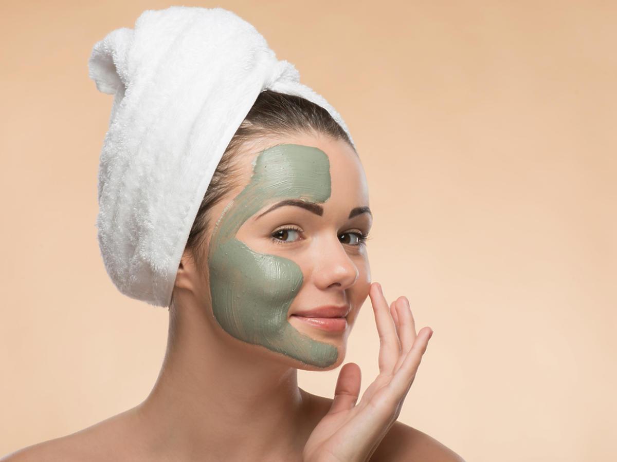 Młoda kobieta nakłada na twarz maseczkę algową.
