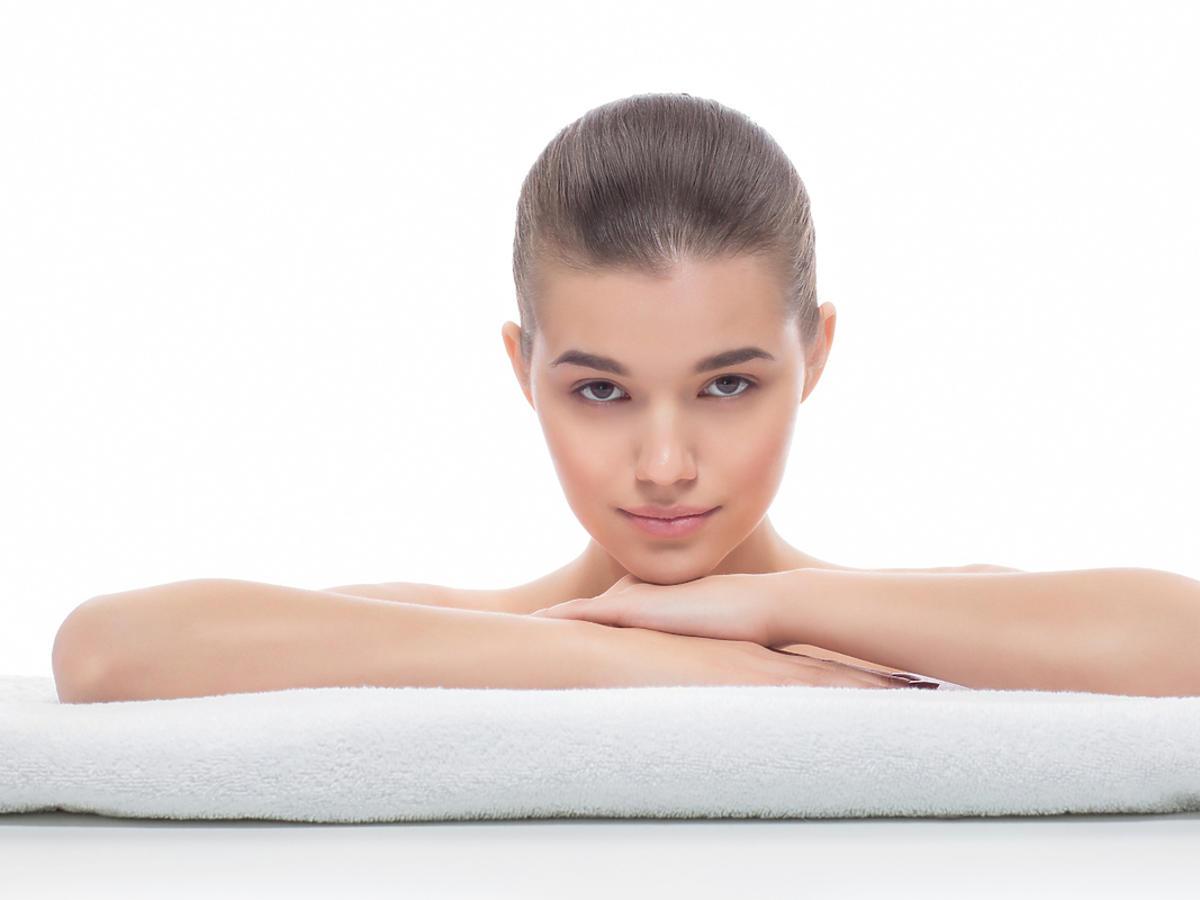Młoda kobieta po zabiegu kosmetycznym, opiera ręce na ręczniku.