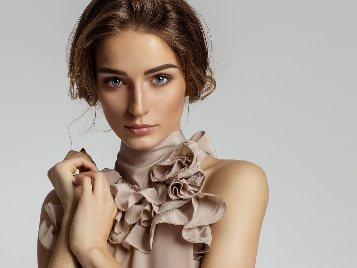 Młoda kobieta pozuje przed obiektywem aparatu w sukience z falbankami.