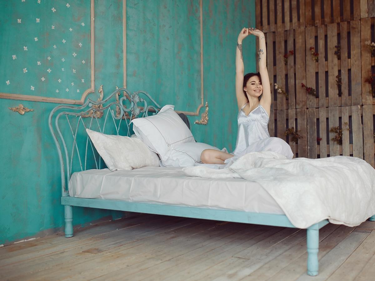 Młoda kobieta przeciąga się na jednoosobowym łóżku.