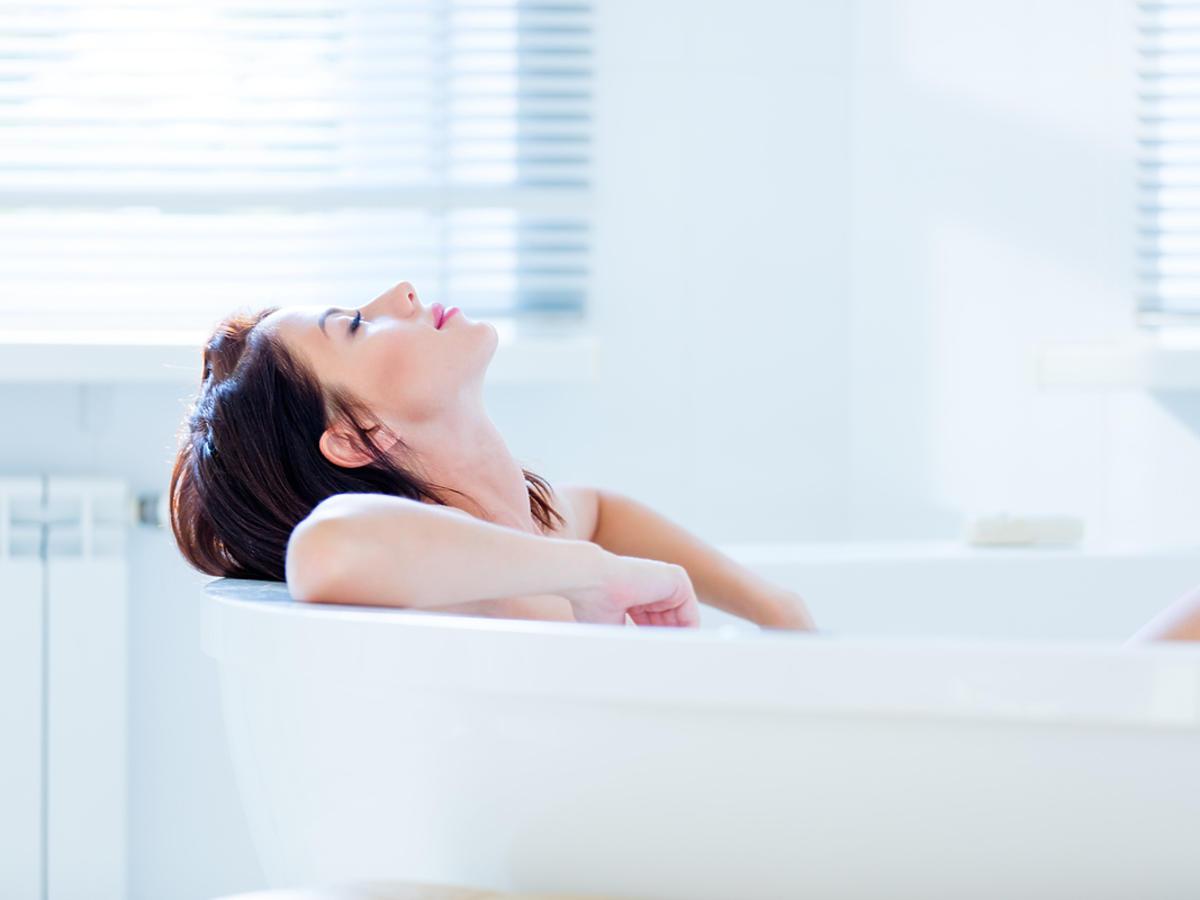 Młoda kobieta relaksuje się w wannie.
