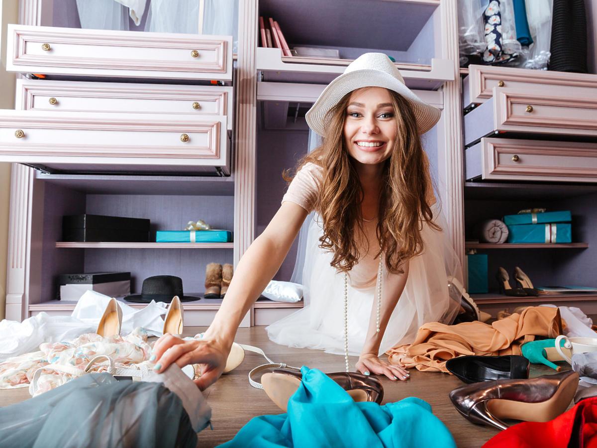Młoda kobieta robi porządek w szafie.