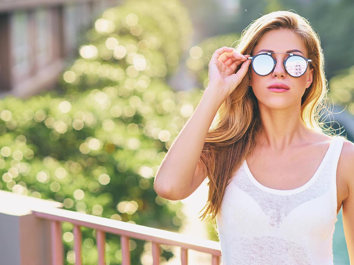 Młoda kobieta spaceruje w okularach przeciwsłonecznych.