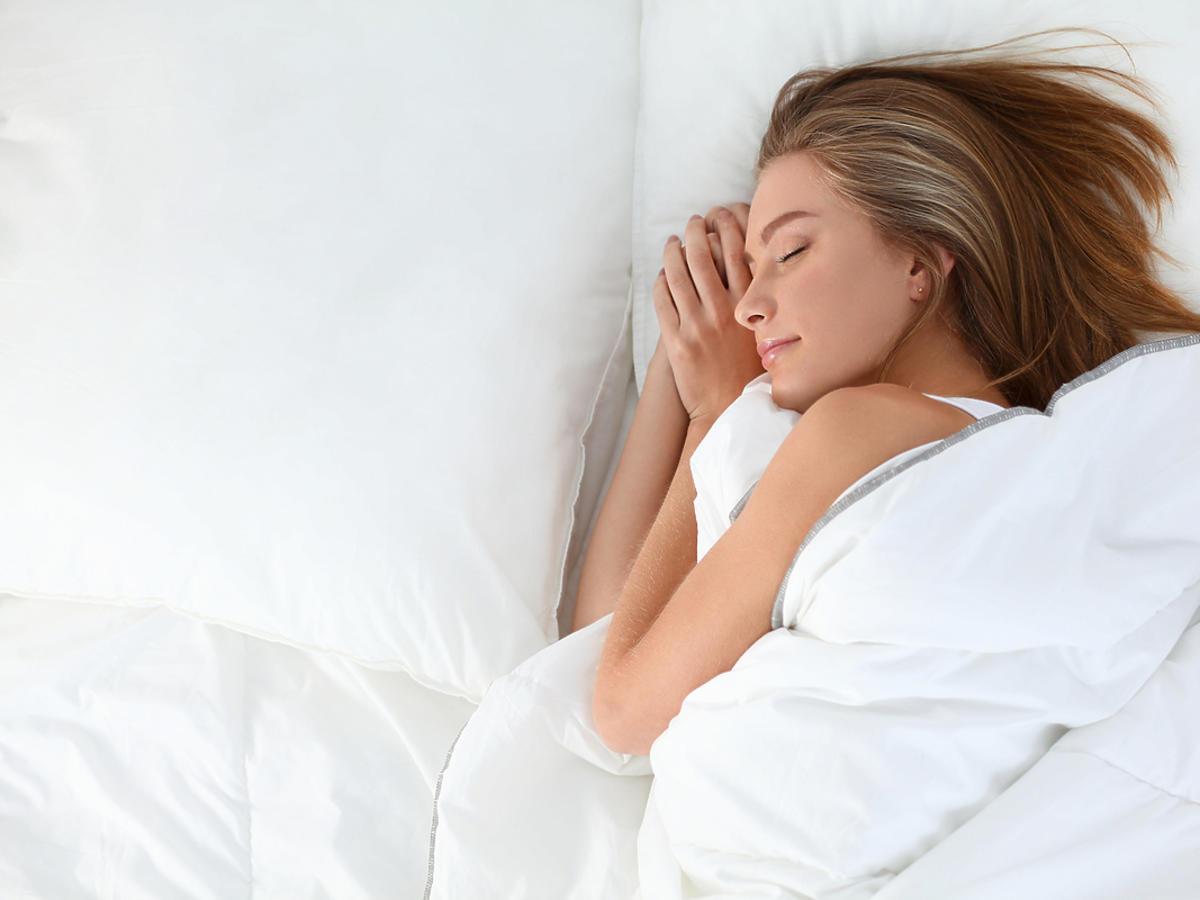 Młoda kobieta śpi na poduszce ortopedycznej.
