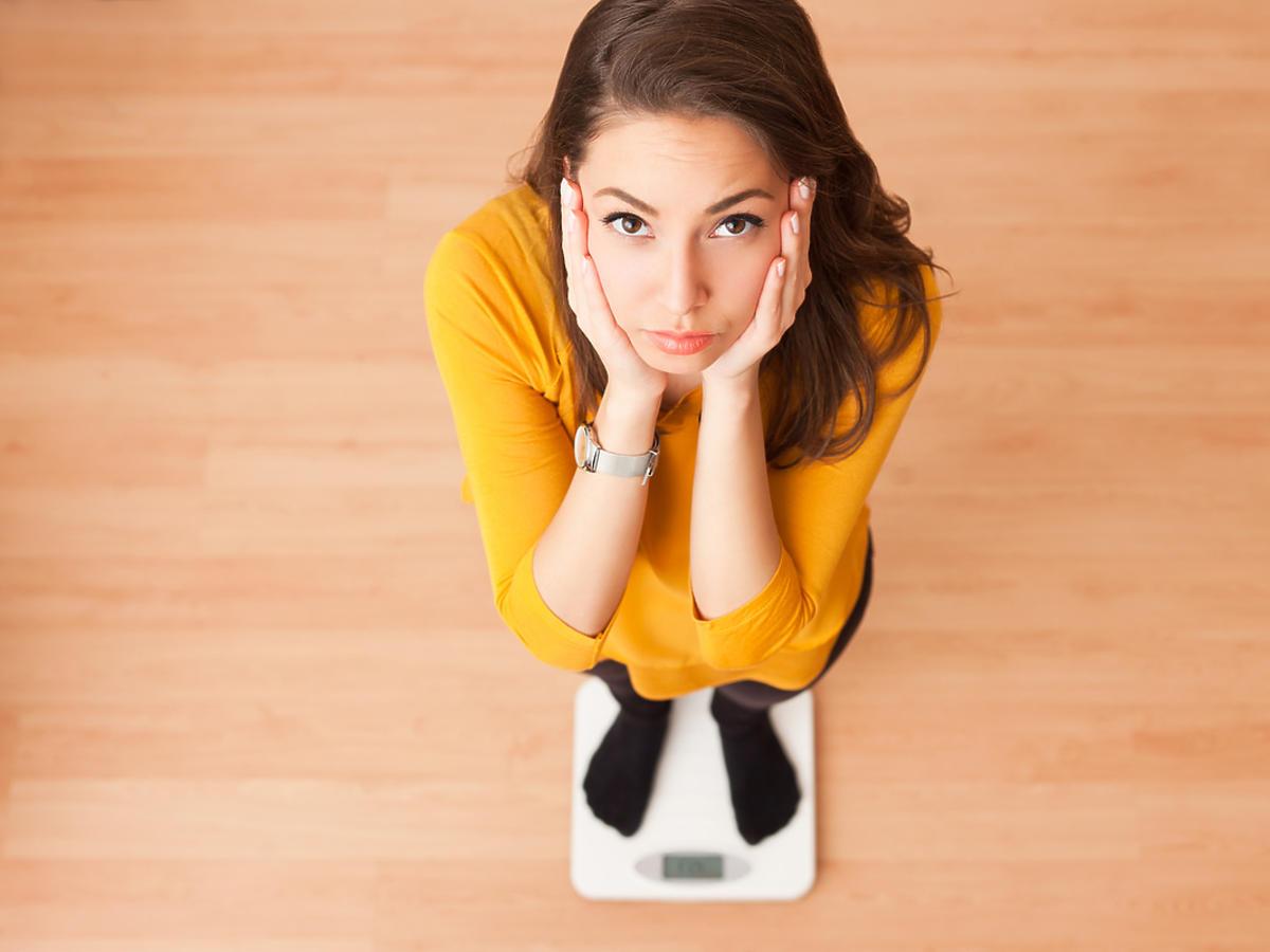 Młoda kobieta stoi na wadze.