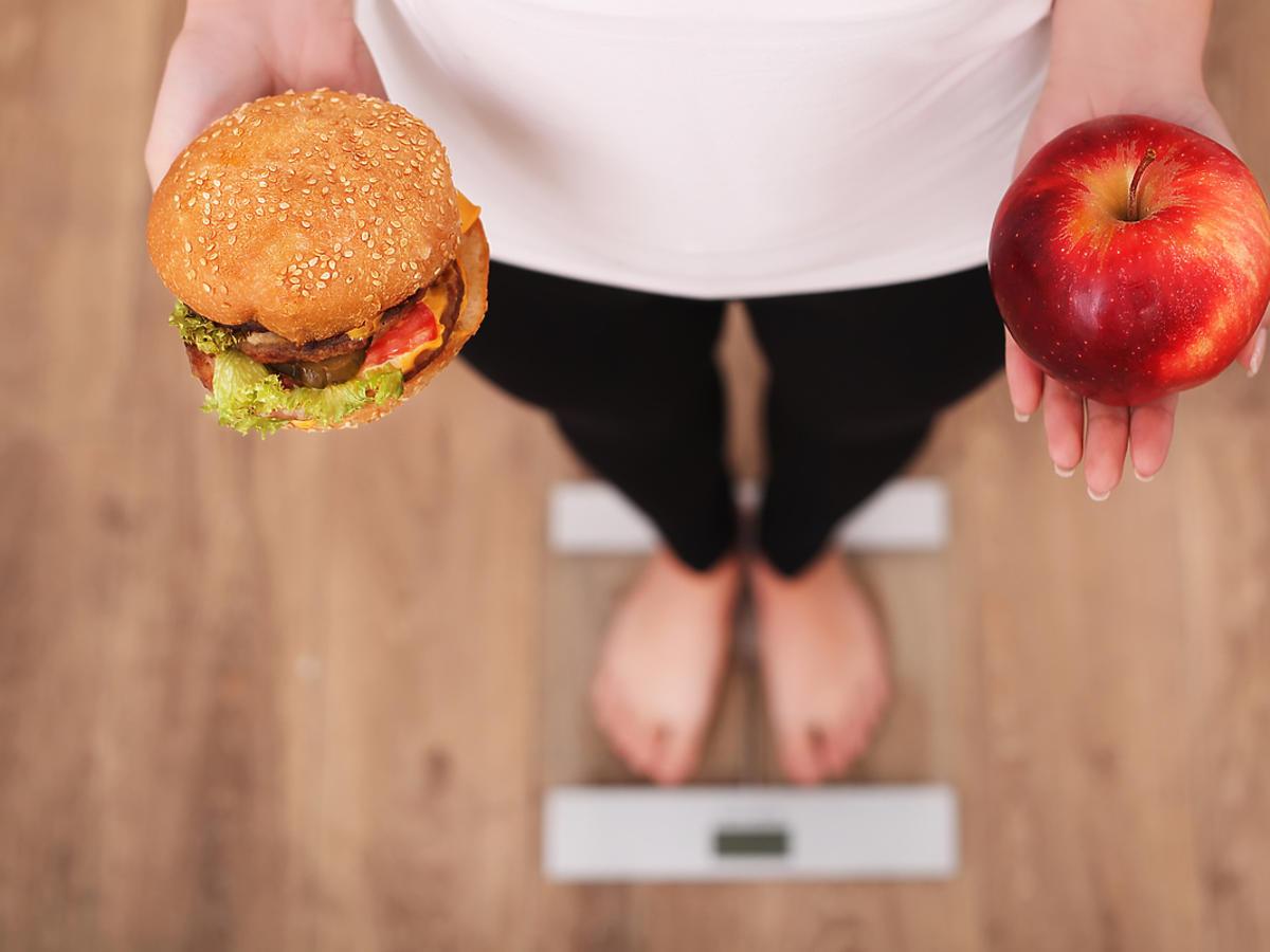 Młoda kobieta stoi na wadze, w dłoniach trzyma burgera i jabłko.