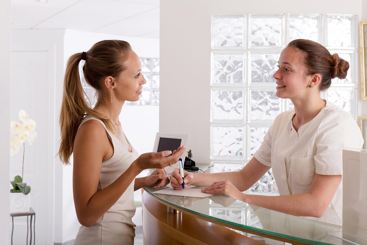 Młoda kobieta stoi przy recepcji w gabinecie ginekologicznym