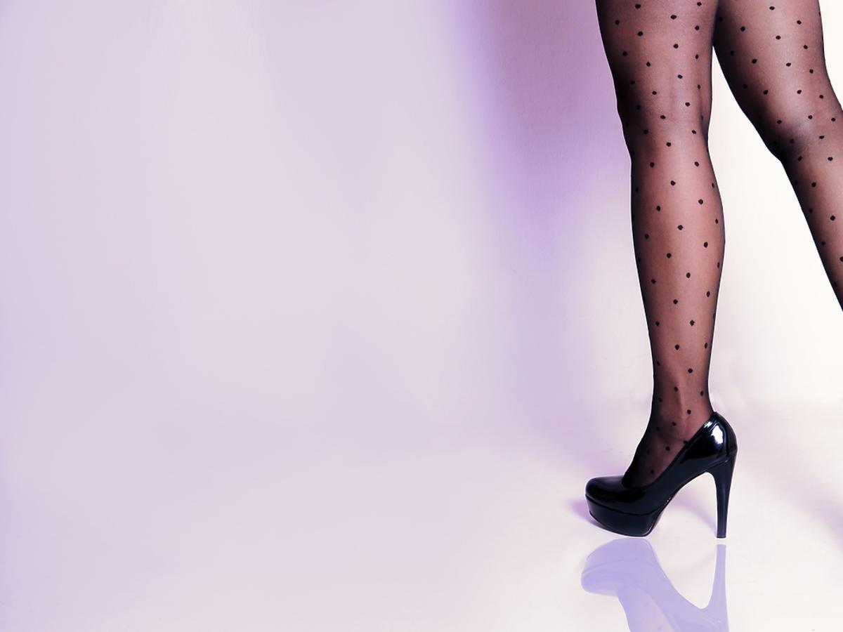 Młoda kobieta stoi w szpilkach i cienkich rastopach w kropki.