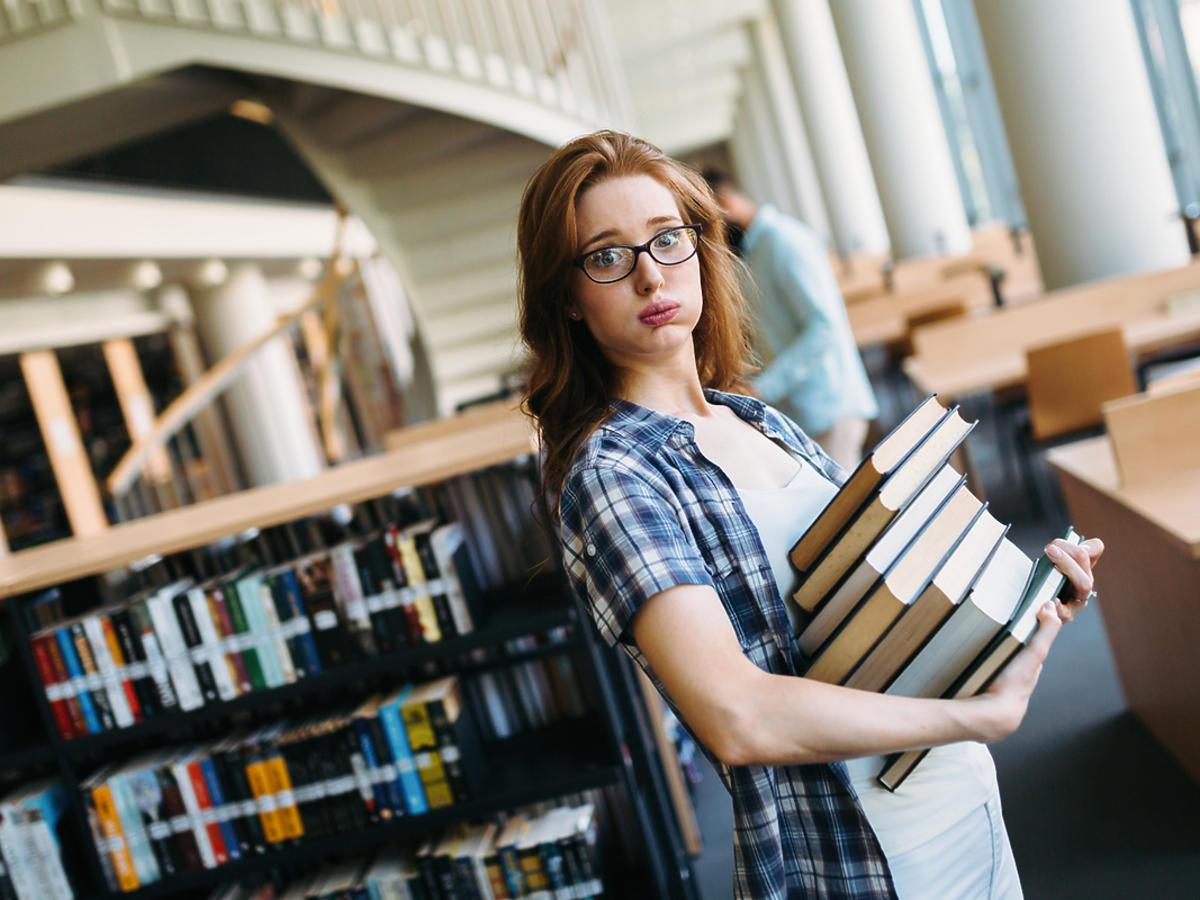 Młoda kobieta stoi z kilkoma książkami w rękach.