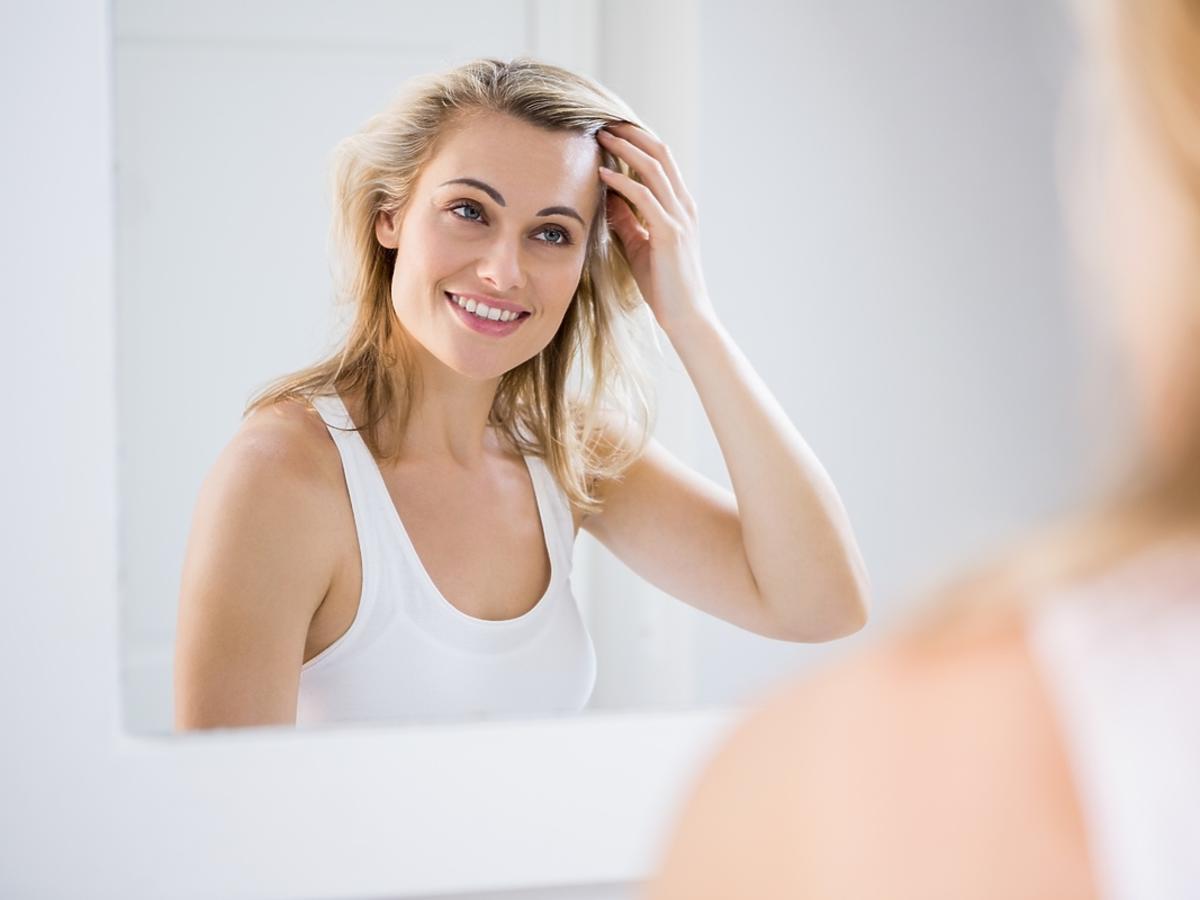 Młoda kobieta szykuje się do wyjścia w łazience.