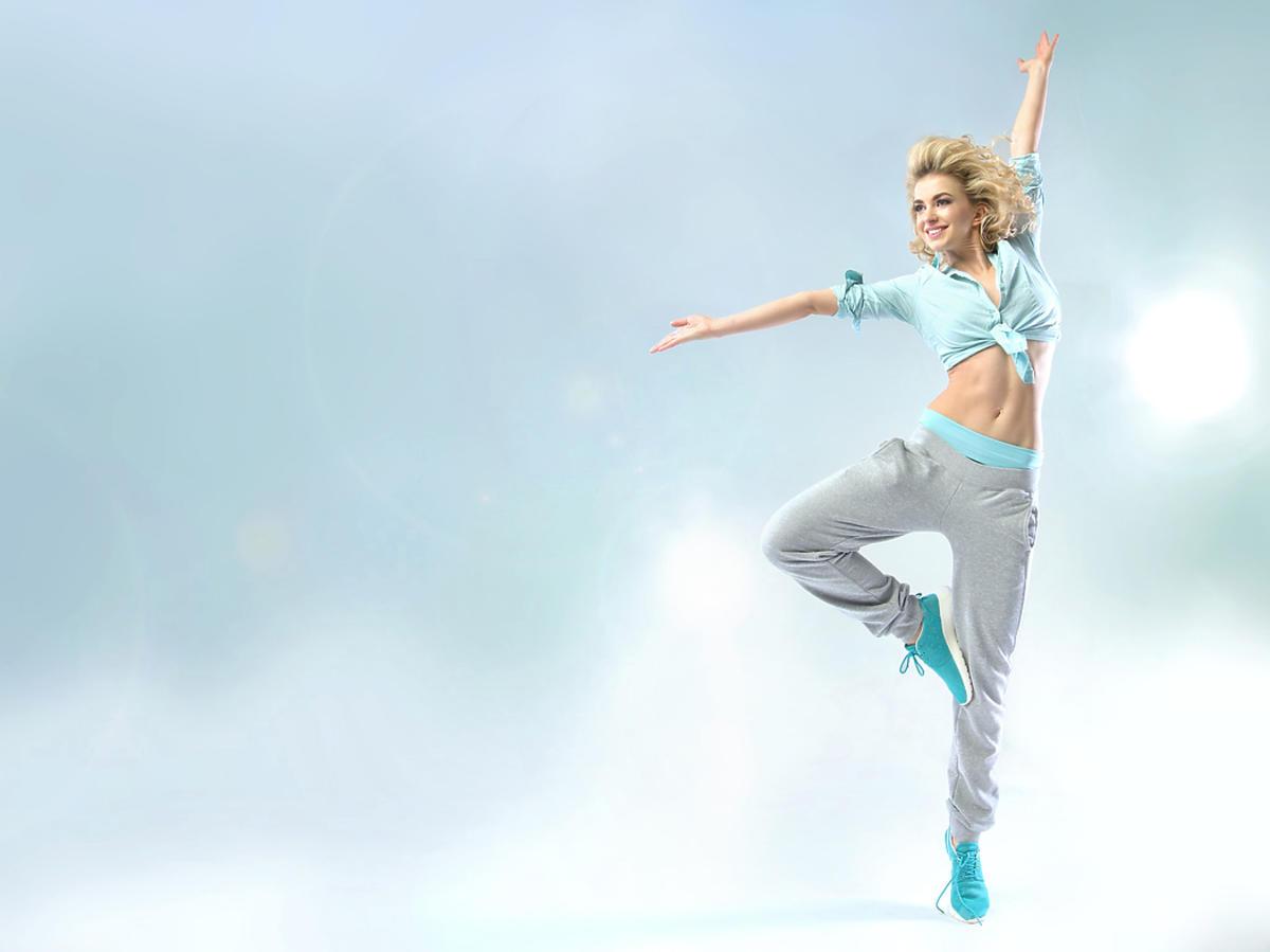 Młoda kobieta tańczy w spodniach dresowych.