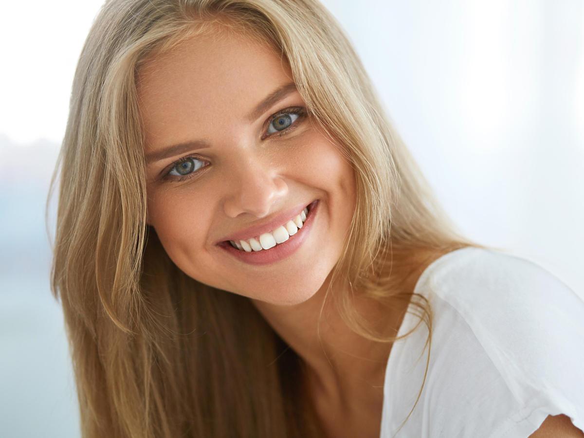 Młoda kobieta uśmiecha się promiennie. Wygląda bardzo naturalnie.