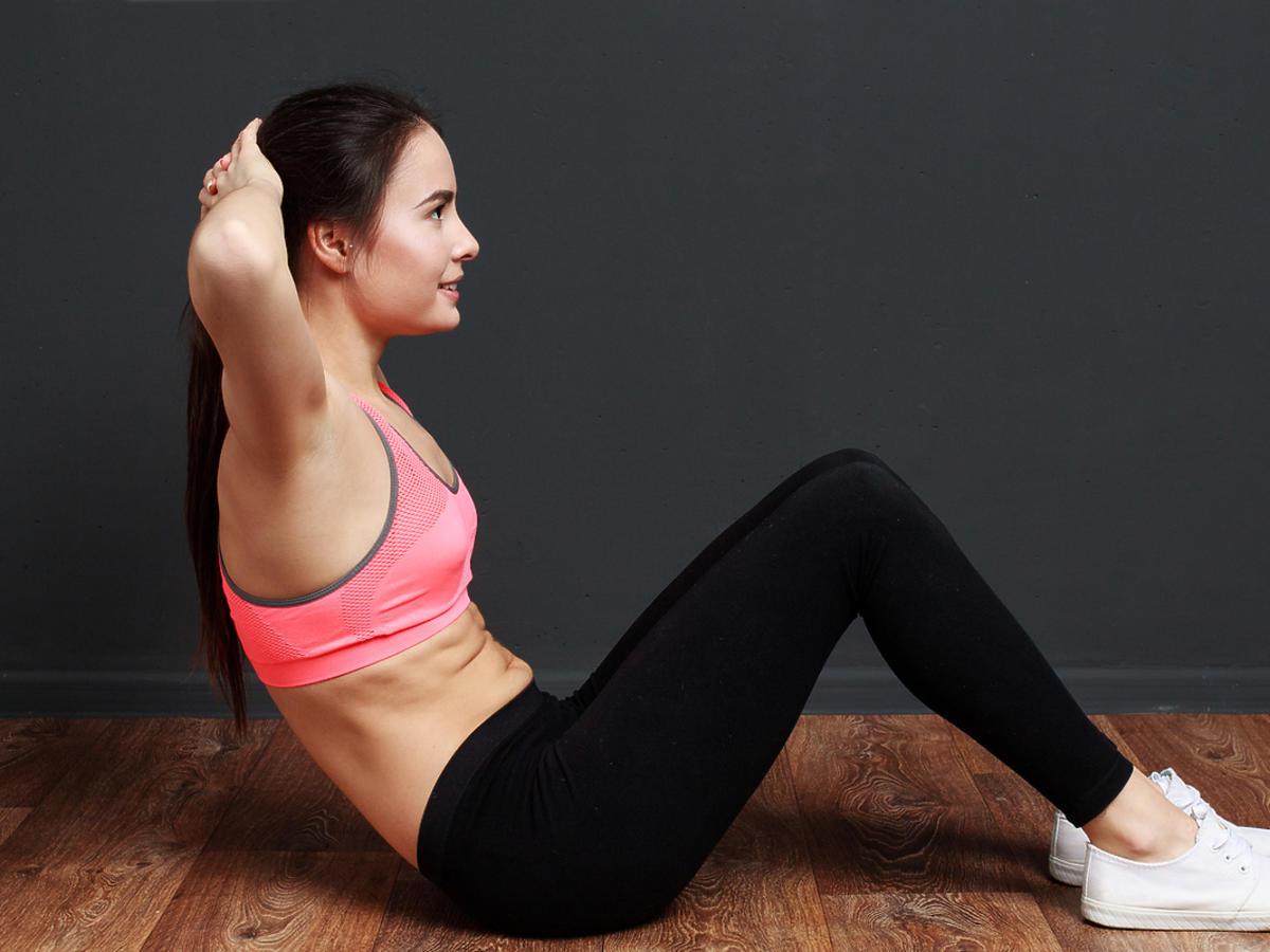 Młoda kobieta w stroju sportowym siedzi na macie i ćwiczy mięśnie brzucha.