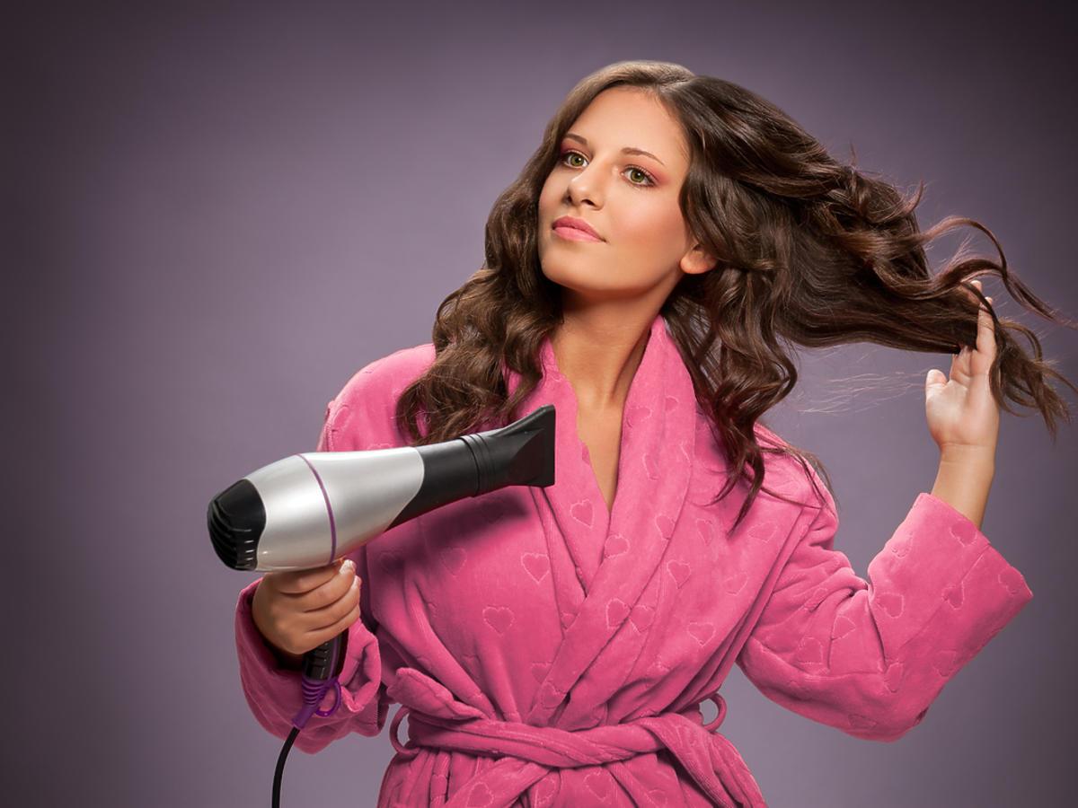 Młoda kobieta w szlafroku suszy włosy suszarką z dyfuzorem.