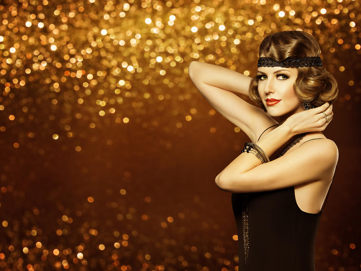 Młoda kobieta w wieczorowym makijażu stoi pod błyszczącą ścianą.