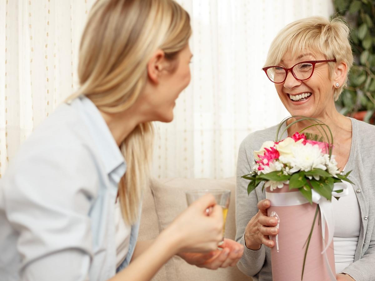 Młoda kobieta wręcza bukiet kwiatów swojej mamie.