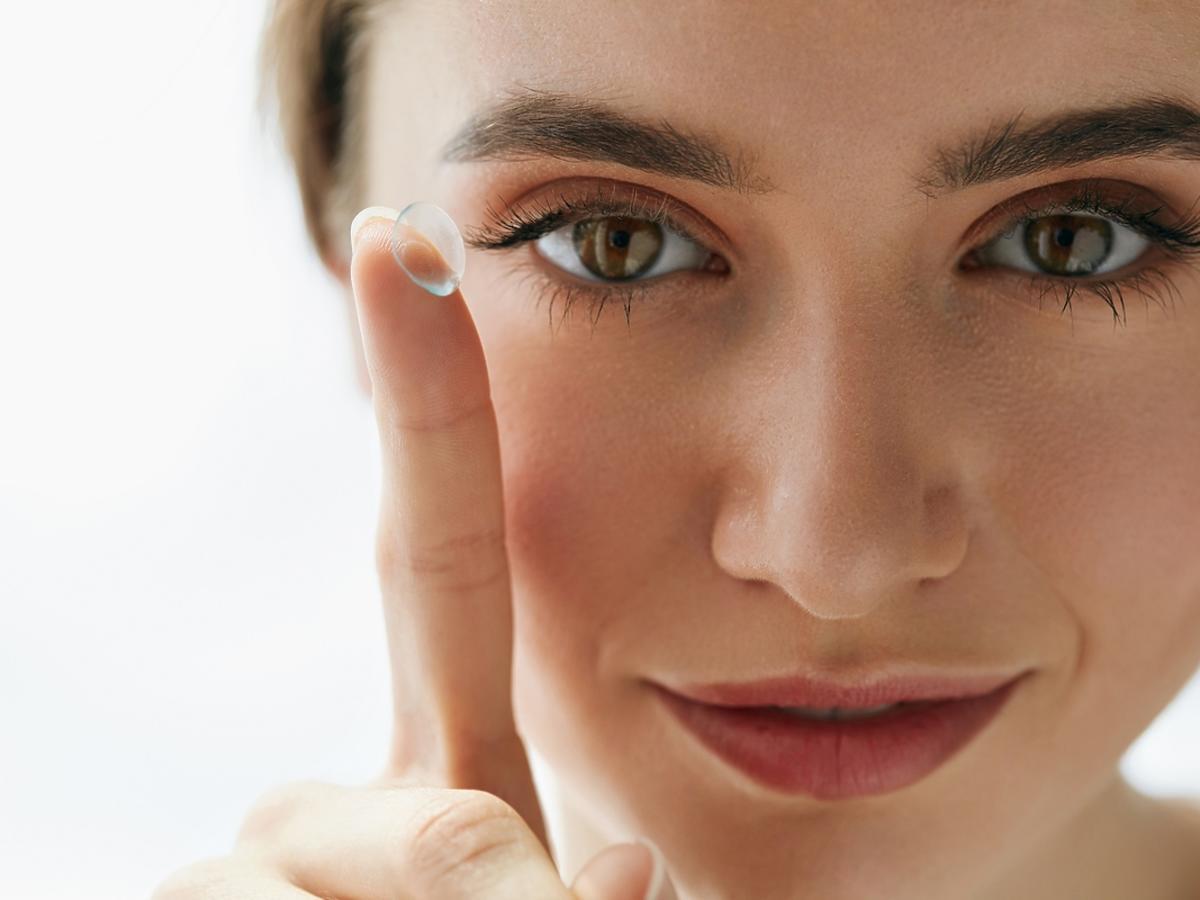 Młoda kobieta zakłada soczewki kontaktowe na oczy.