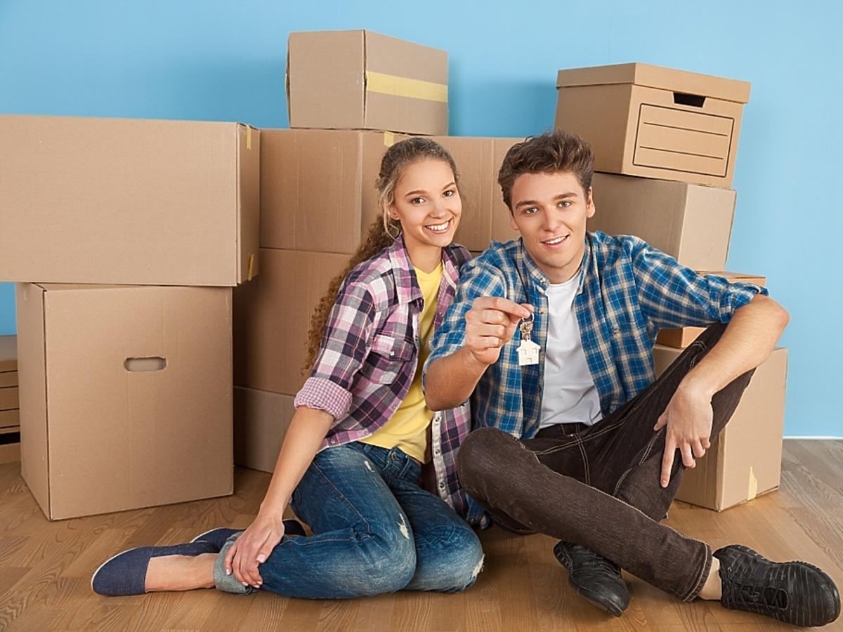 młoda para wprowadza się do nowego mieszkania - za nimi kartony