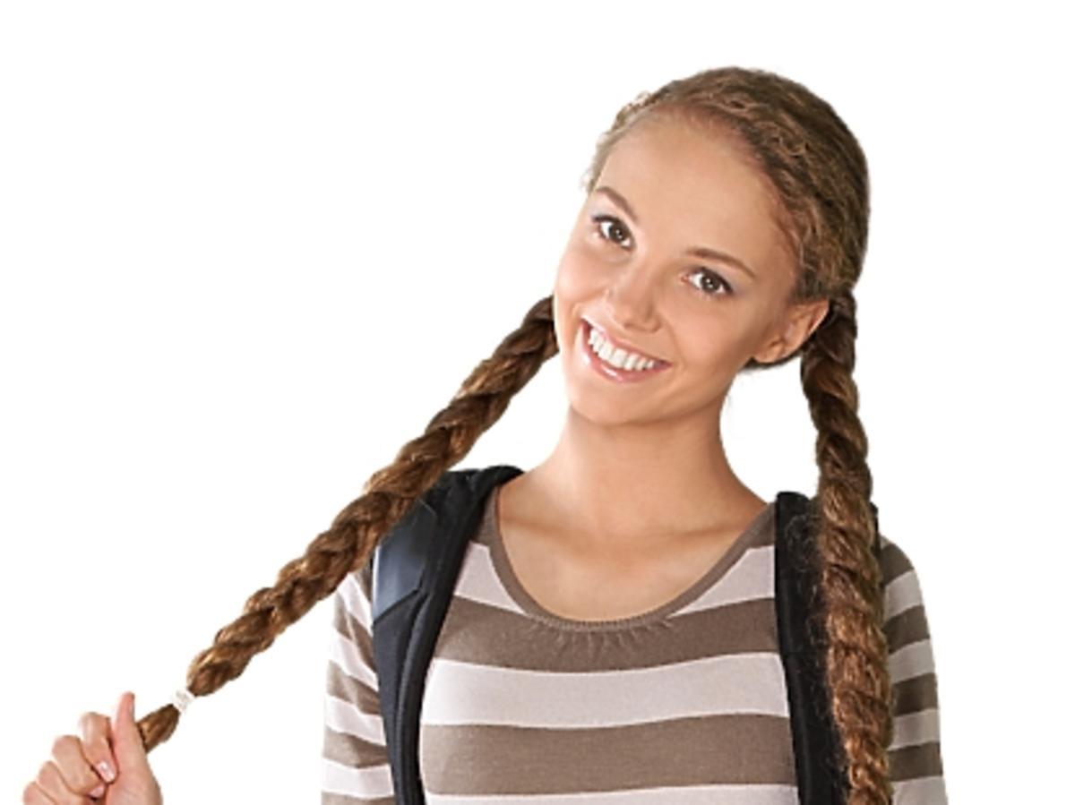 młoda uśmiechnięta dziewczyna trzymająca się za swoje długie warkocze