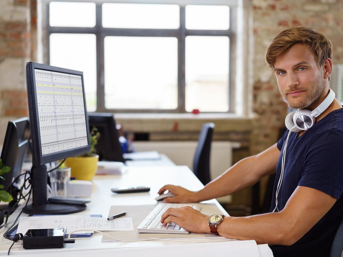 Młody chłopak siedzi przy biurku, przed sobą ma monitor komputera