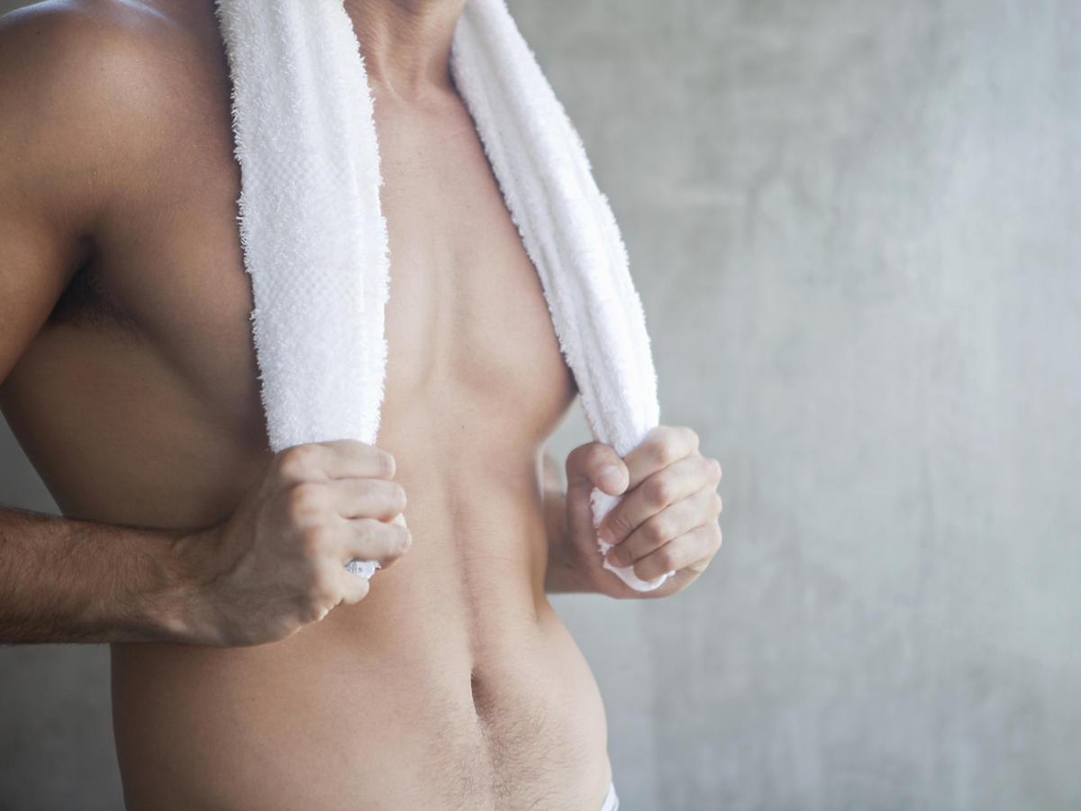 Młody mężczyzna bez koszulki stoi okryty ręcznikiem.