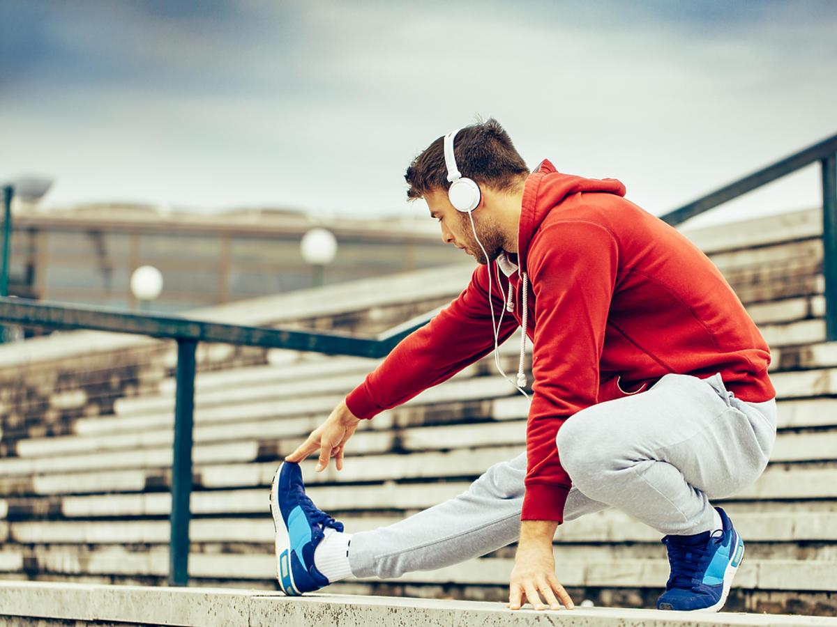 Młody mężczyzna rozciąga się przed bieganiem.