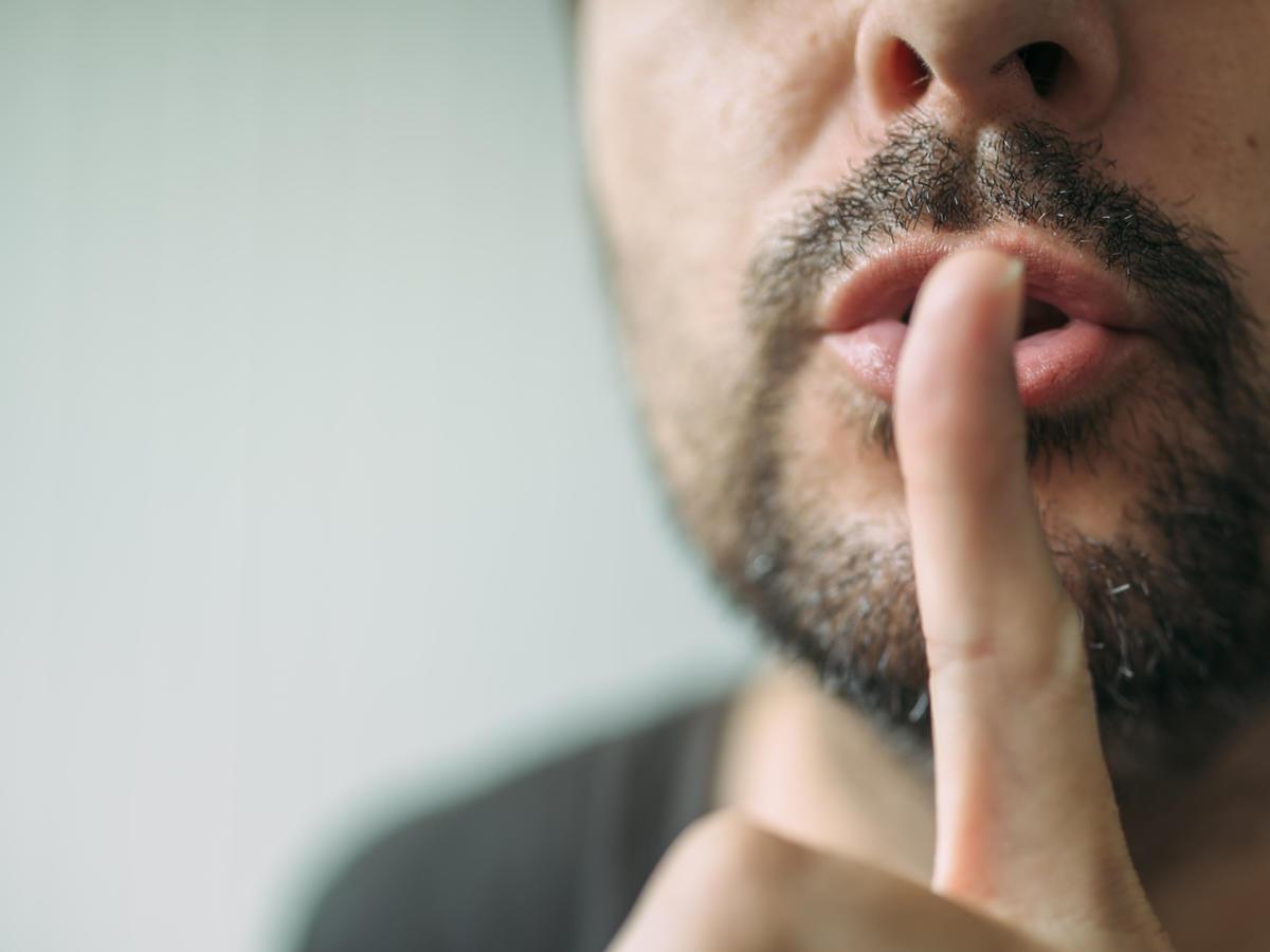 młody mężczyzna trzymający palec na ustach