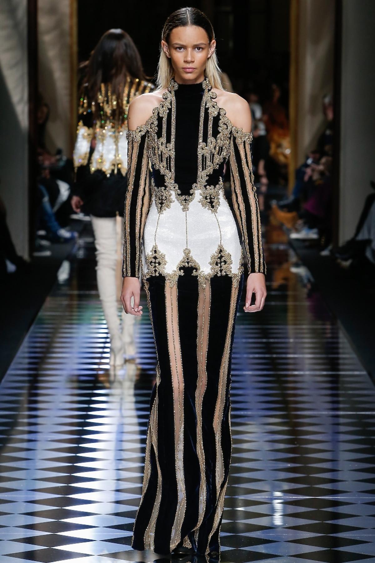 Modelka na wybiegu w długiej czarno-złotej sukni w pasy